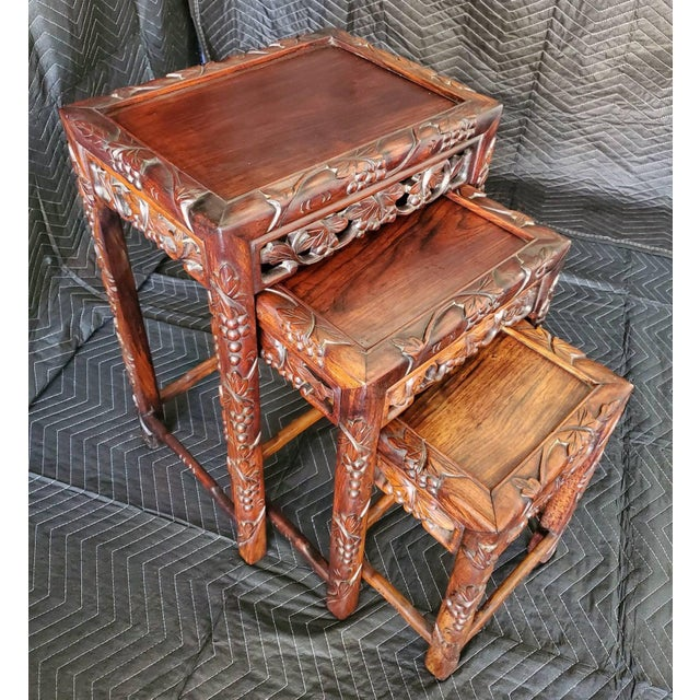 Stunning set of three exquisitely carved Chinese hardwood nest of tables. Handcrafted in the early 20th century, featuring...