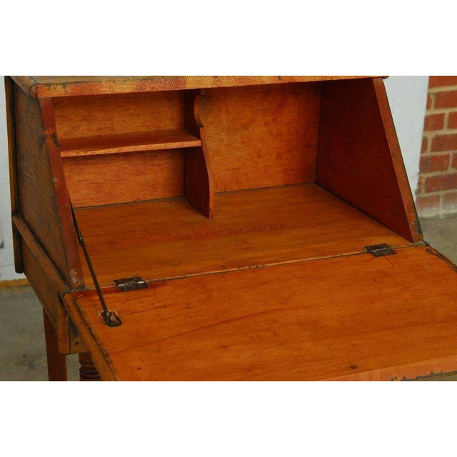 19th century diminutive slant front desk constructed from mostly pine having a rustic finish. The drop down front opens to...