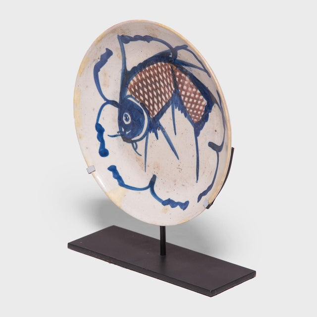 A traditional motif in Chinese art, the fish on this hand-painted 19th-century provincial plate represents a blessing for...