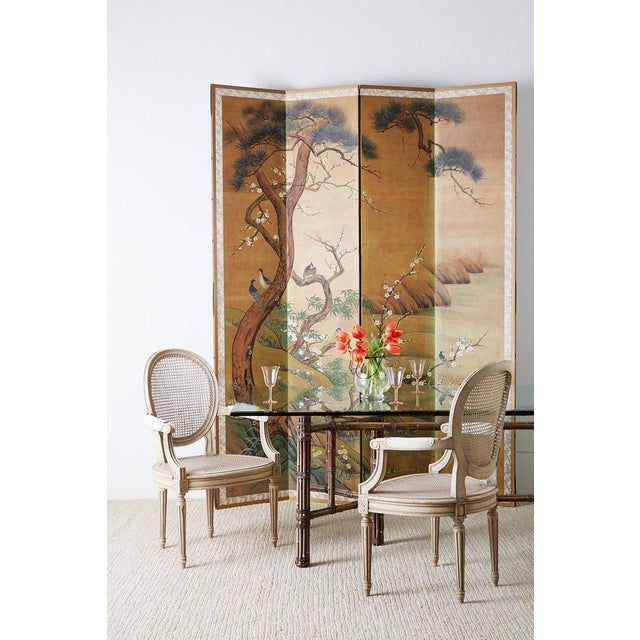Monumental Japanese four-panel folding screen made in the Edo period style. Depicts an idyllic spring landscape scene with...