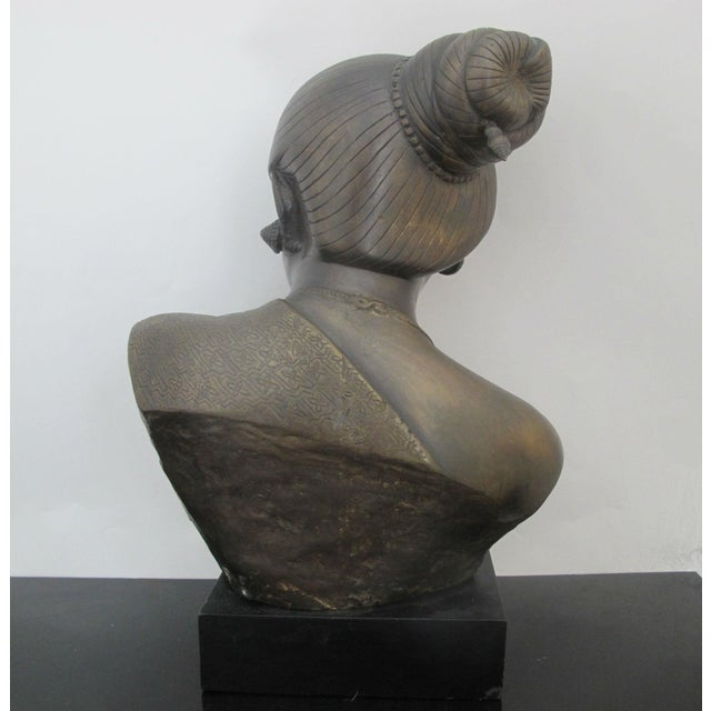 Lovely bronze sculpture of finely detailed Burmese female bust on stand. Her hair is pulled back and she wears detailed...
