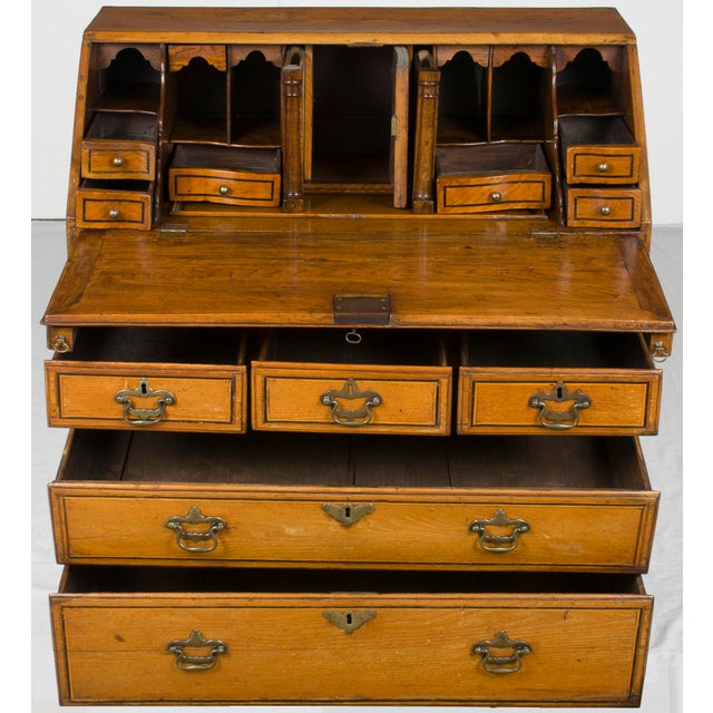 This antique bureau desk was hand-crafted in Victorian England around the year 1870. Today the faded, light oak wood fits...