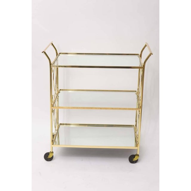 Winsome polished brass Italian drinks trolley or tea cart. This three-tiered Italian beauty has two glass shelves floating...