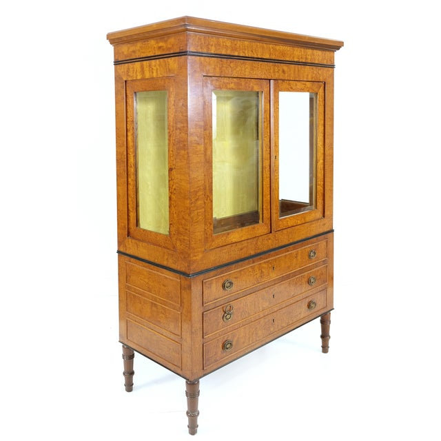 Offered for sale is a Neoclassical style vitrine with glass shelves and drawers below from Rho Mobili D' Epoca of Italy....