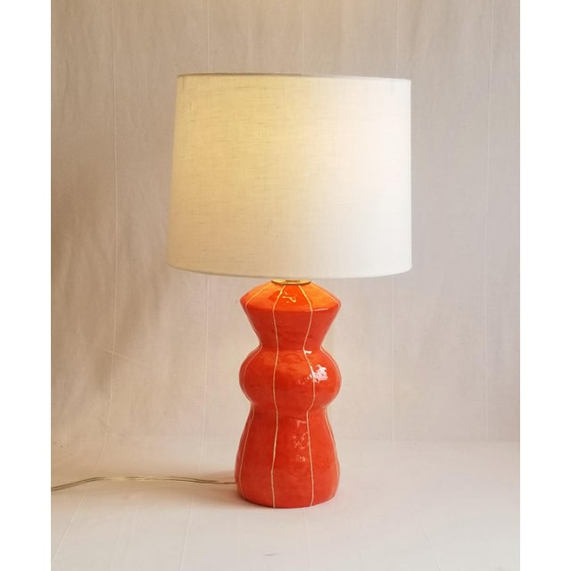 This contemporary, mid-century inspired, coral red table lamp was handmade at kRI kRI Studio in Seattle. The soft,...