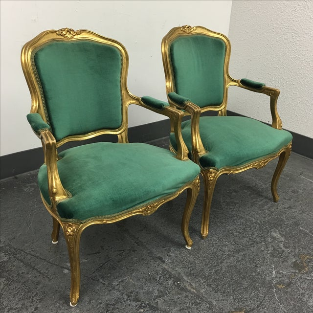 A pair of vintage, Louis XV chairs that have been upholstered in a warm green, velvet fabric. The chairs are framed in a...