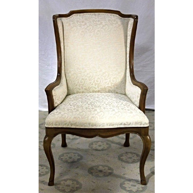This French Provincial custom upholstered armchair with white winged back is the epitome of uncomplicated beauty, and you...