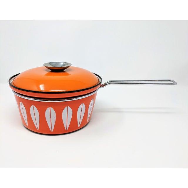 Mid-century Cathrineholm large enameled saucepan by Grete Prytz Kittelsen. In orange, with Cathrineholm's distinctive...