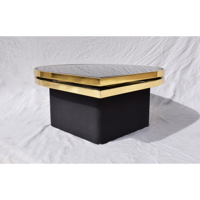 Elegant reverse black painted glass and brass cocktail or coffee table with floating upholstered base designed and...