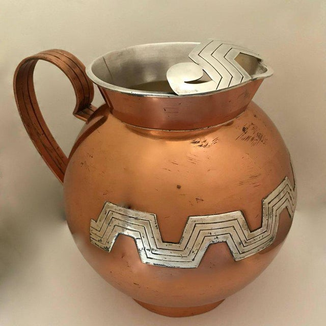 A beautiful moderne copper water pitcher by Victoria of Taxco, Mexico. Hand hammered and created from sheet metal, this...
