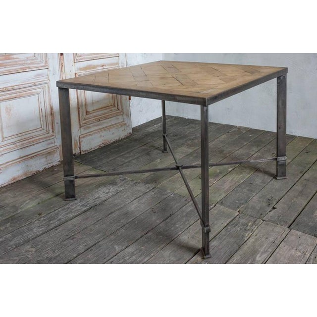 Square table with hand crafted iron frame (made in the 1990s). The top of the table is parquetry wood flooring from a 19th...