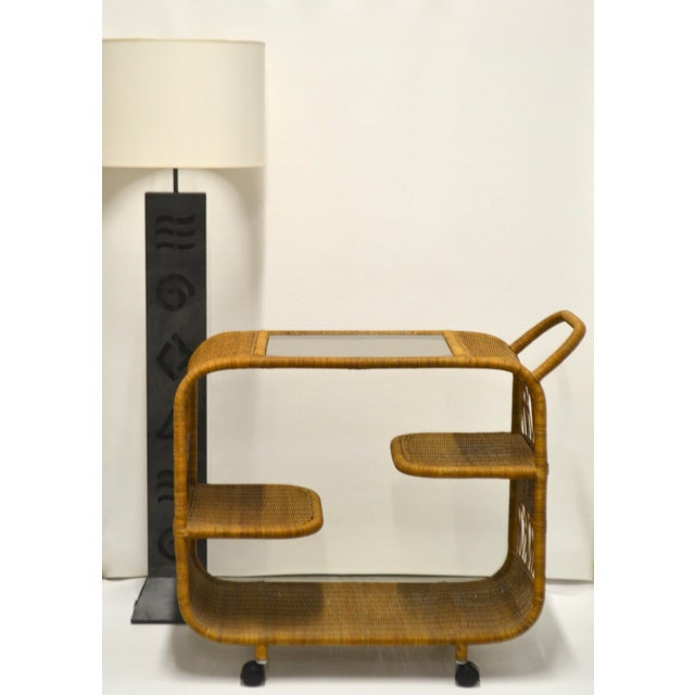 Stunning Mid-Century woven rattan bar cart, c. 1960s -1970s. This sleek serving cart is designed with an inset smoked...