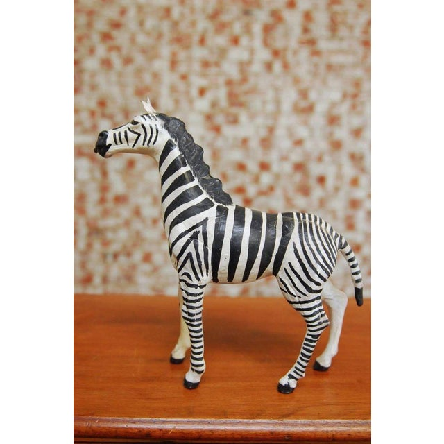 Charming midcentury leather wrapped African zebra sculpture featuring a hand-painted body. Vintage life-like leather with...