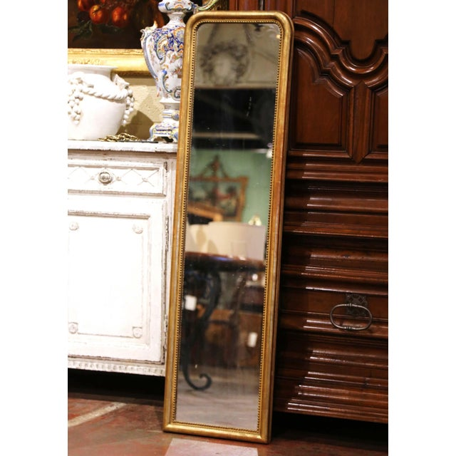 Decorate a dressing room or hallway with this elegant tall and narrow antique gold leaf floor mirror. Crafted in the...