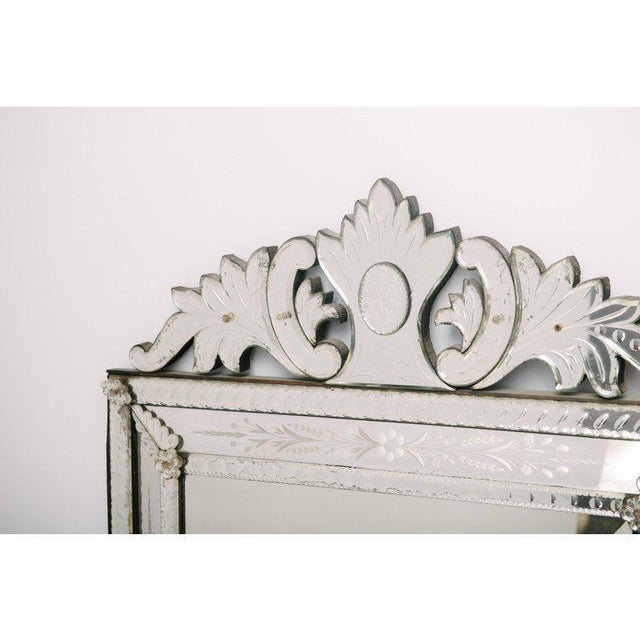 Stunning etched and beveled Venetian glass mirror, circa 1920. This antique Venetian mirror is in great condition with...