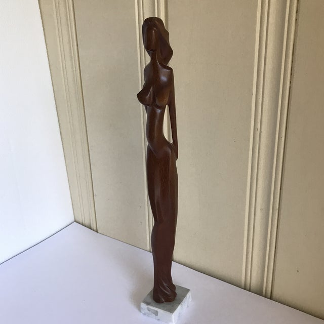 Tall slender Midcentury wood sculptural figure of a female nude on a small marble or alabaster platform. Beautifully...