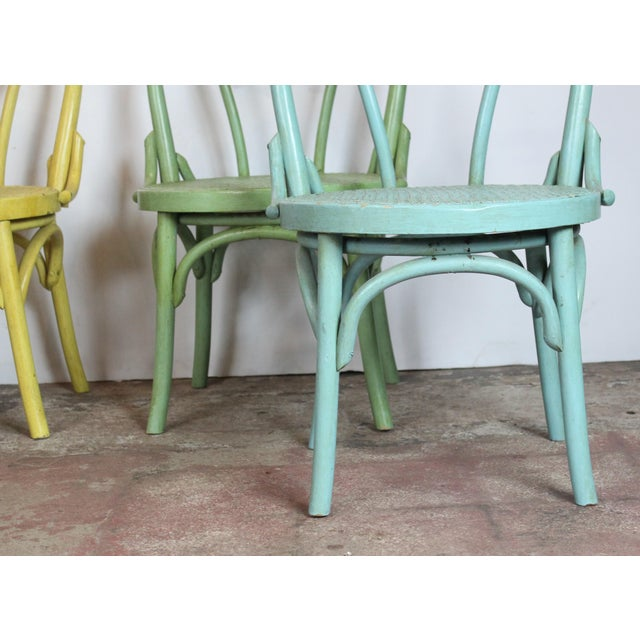 Set of four painted bistro chairs with cane seat. Perfect for hosting brunches with guests.