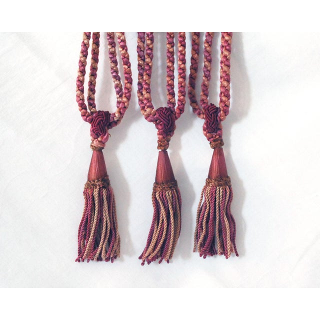 Three vintage curtain or drapery tiebacks with tassels in faded shades of pink and wine red (verging on brown in some...