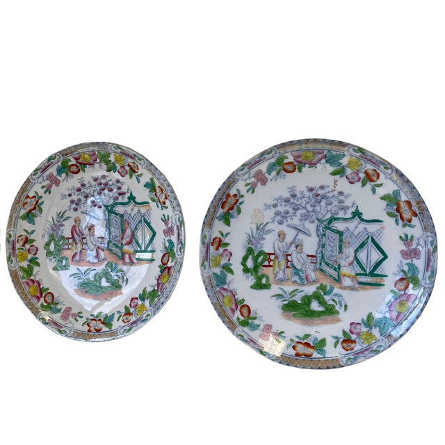 A pair of colorful green, gold, yellow and pink Chinese plates with three figures.