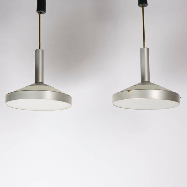 Rare set of two pendant lamps by Stilux. Frosted glass shades with bottom and top lighting diffusion, aluminum frame and...