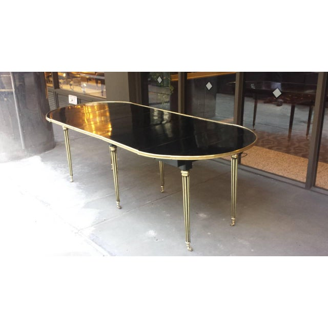 Exquisite Maison Jansen 7 1/2 ft. ebonized mahogany dining table with brass banding on fluted legs ending in brass...