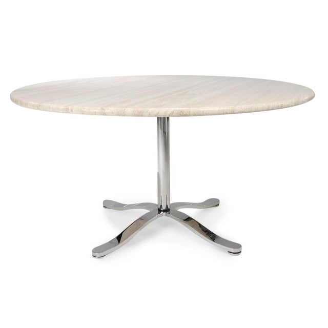 A chic center or dining table with a circular travertine top supported by a substantial chrome plated steel four prong...