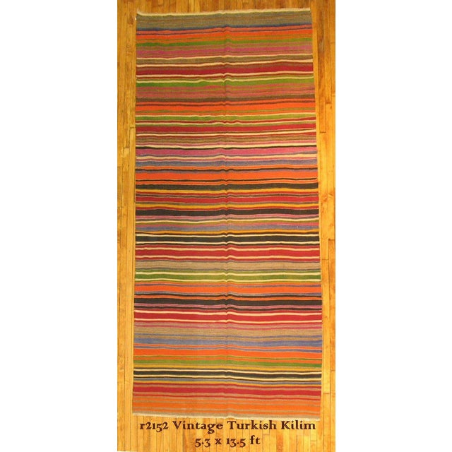 One-of-a-kind turkish kilim flat-weave rug. Features orange, red, yellow, green, brown, and blue striped in no particular...