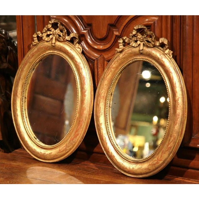 This beautiful pair of antique mirrors was crafted in Paris, France circa 1780. The classic, oval, wall hanging mirrors...