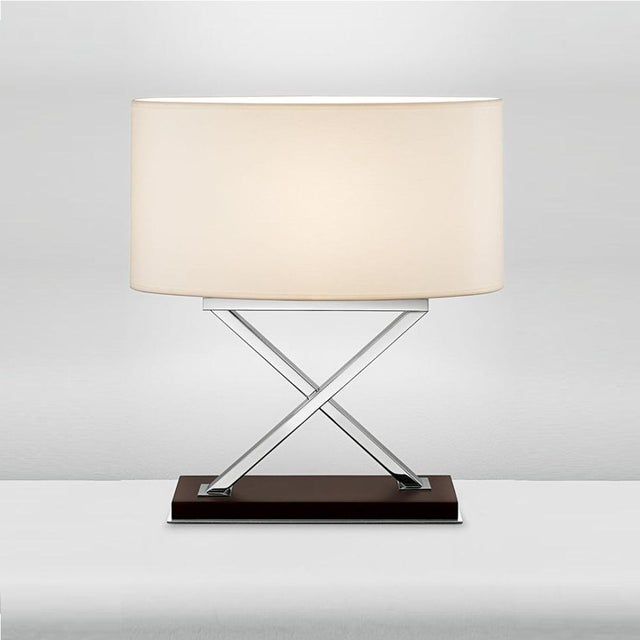 Polished chrome table lamp on chocolate coloured wood base. The crossover sections pass one in front of the other and the...