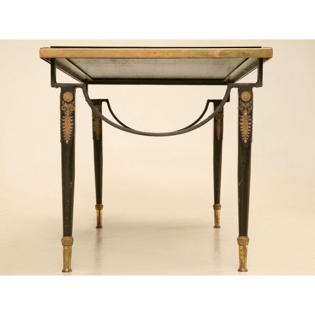 Mesmerizing vintage French brass coffee table with black accents and ormolu trim. This coffee table will knock your socks...