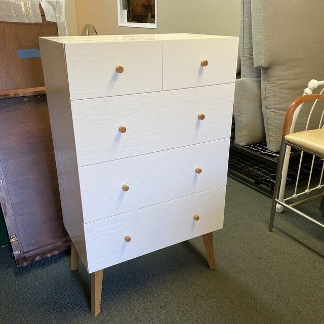 Design Plus Gallery presents a West Elm Mid-20th Century Style Tallboy Dresser. A utilized modern take on mid-20th century...