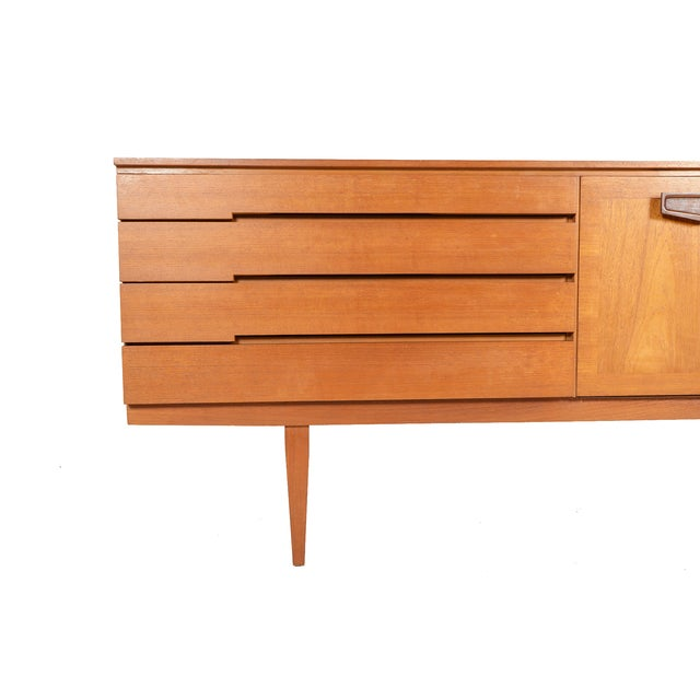 This long and low English Mid-Century Modern credenza by Beautility offers clean Danish lines with tasteful detailing....