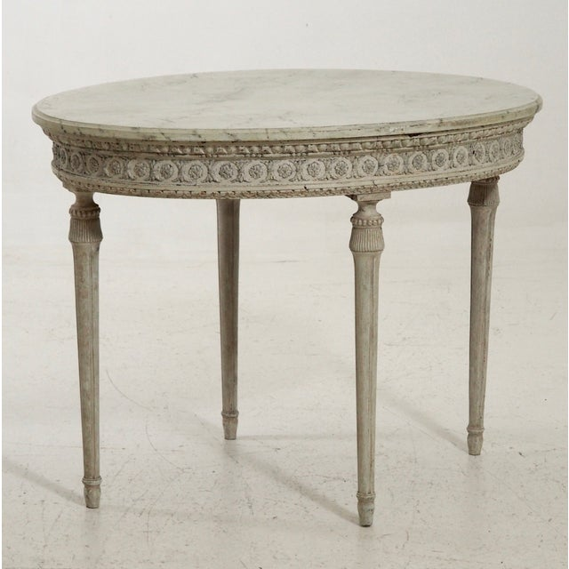 This 19th C Oval Swedish side table features a richly carved apron. Item Arrival into New Orleans January 2019.