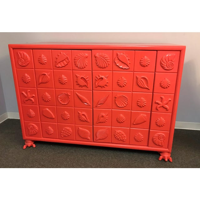 Wow! This gorgeous cabinet won't last long! The wood cabinet has various seashell designs in a gridlike pattern and is...