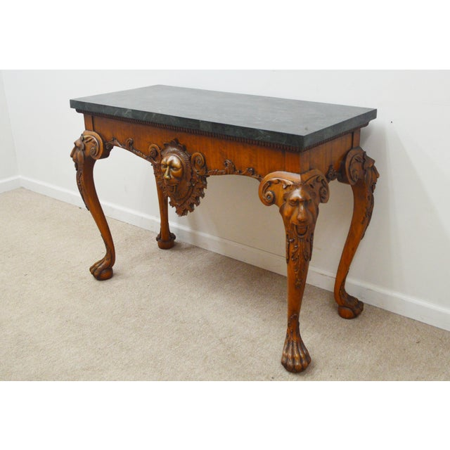 Console Table by Maitland Smith. It features a lacquered top, carved heads and paw feet.