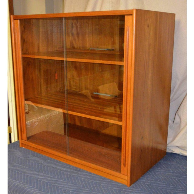 Midcentury teak storage cabinet from Denmark. Wired for electronics with sliding glass doors. A Classic period piece in...