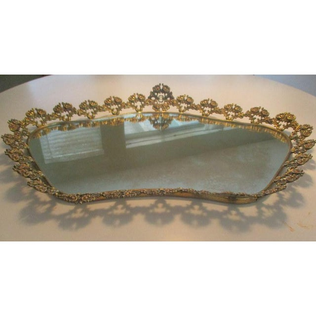 Lovely oblong vintage plateau mirrored tray featuring brass stylized flowers all around. A heavy, very sturdy piece, with...