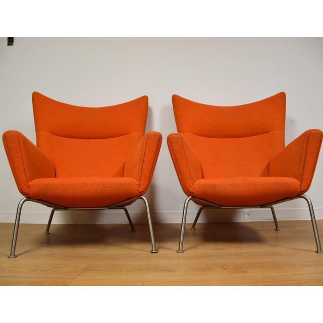 A beautiful pair of Danish modern CH445 orange lounge chairs by Hans J. Wegner for Carl Hansen. Internal solid beech frame...