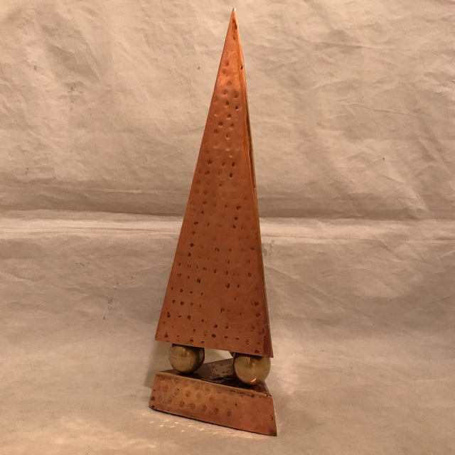 Artisan hand hammered copper and brass pyramidal obelisk mounted on three brass spheres. Hammered copper base with felt on...
