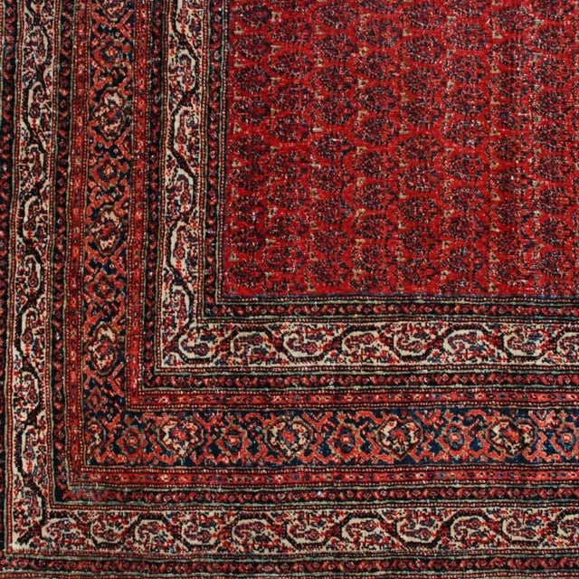 A late 19th century Persian Seraband carpet with all-over paisley pattern on a crimson background surrounded by multiple...