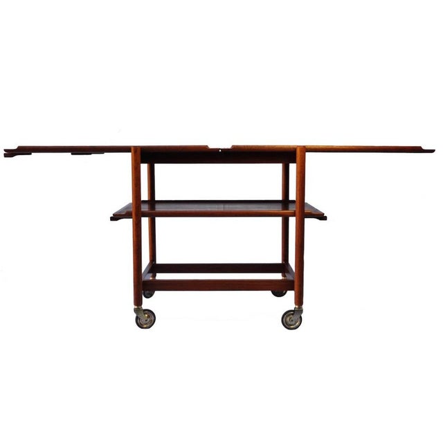 A triplex bar cart in richly aged teak with plated metal and rubber wheels. Either of the bottom platters can be removed...