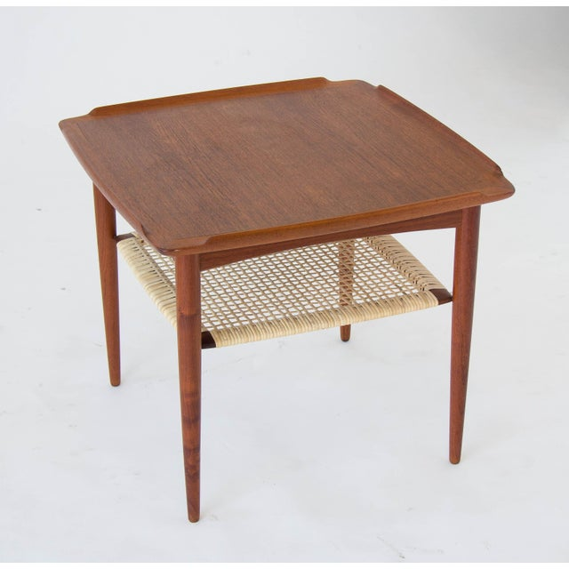 A square teak side table with a cane shelf. Designed by Poul Jensen and imported to the US by Selig, the table has a solid...