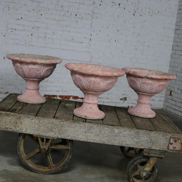 Awesome set of three antique concrete garden urns. These salmon colored paint encrusted vintage urns are in fabulous...