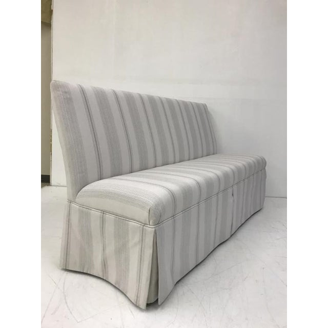 The Skirted Armless Banquette is a first quality market sample that comes in a striped fabric. It features a Kick Pleat...