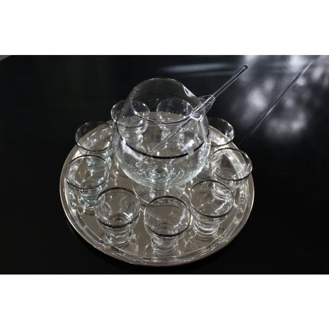 A lovely martini or drink set. The martini set features: a pitcher, tray, 9 glasses and a stirrer. In the manner of...