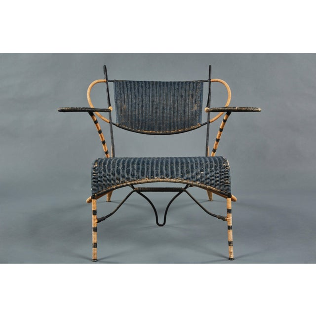 A unique and sculptural Italian black and natural wicker chair over a steel frame. Its flamboyant elements contributing to...