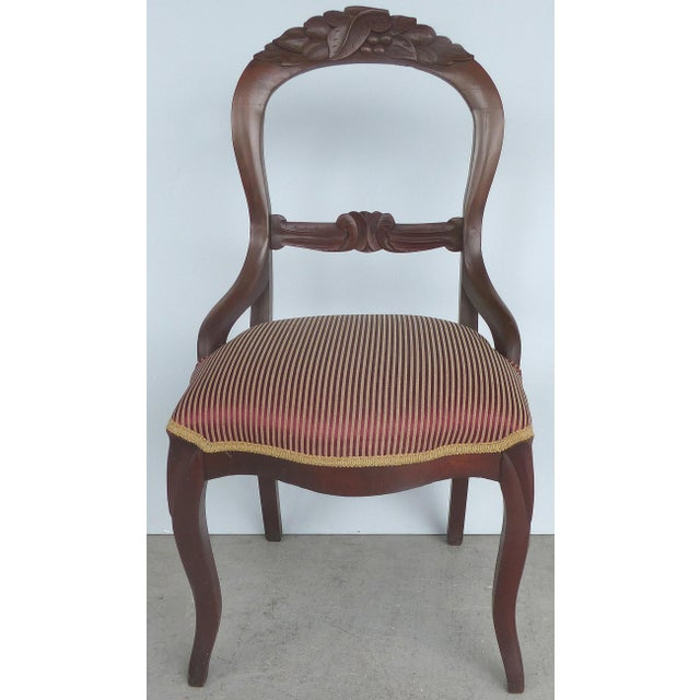 Offered for sale is a pair of mahogany dining chairs in a Balloon Back style with carved details. The chairs are...