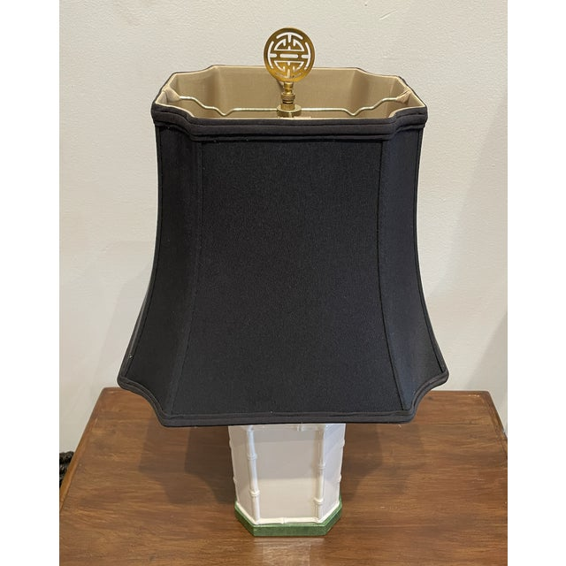 White porcelain lamp with bamboo shaped embellishments supported by green stone. Black pagoda shade is enhanced by brass...