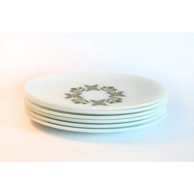 A wonderful set of oval dinner plates. These large dinner plates are milk glass and are embellished with a green floral...
