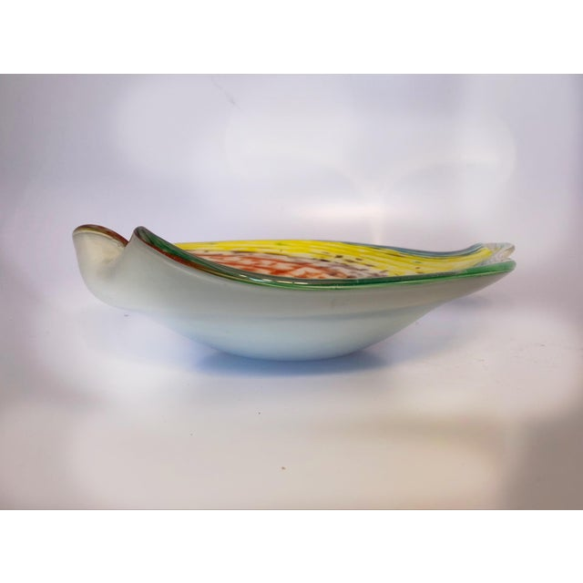 A mid-century modern Murano cased bowl with multiple colors of yellow, red, blue, green swirls and goldflecks running...